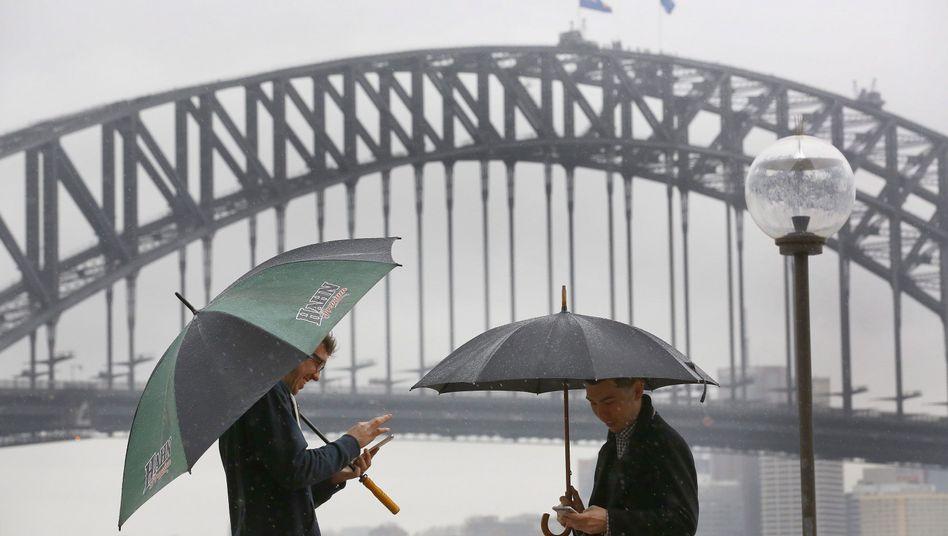 Spazieren im Regen? Lieber nicht! Aber spielen, wie diese Männer in Sydney