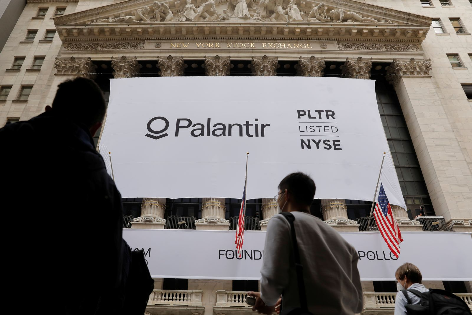 People walk by a banner featuring the logo of Palantir Technologies (PLTR) at the New York Stock Exchange (NYSE) on the day of their initial public offering (IPO) in Manhattan, New York City