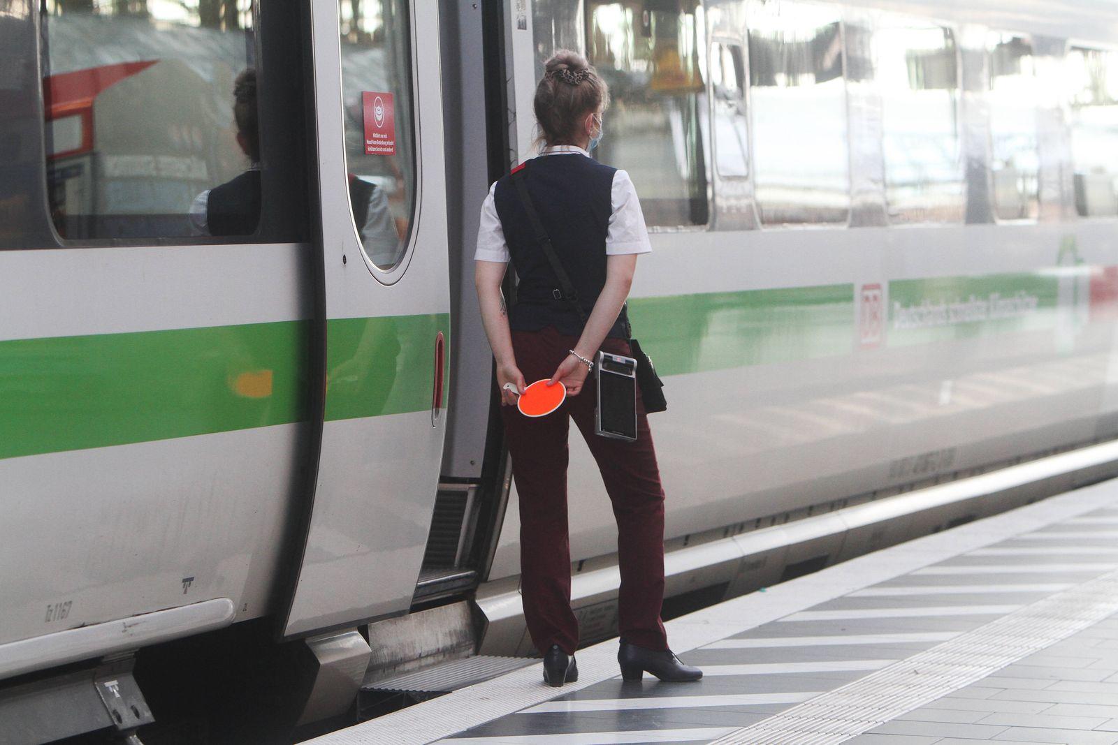 Zugbegleiterin der DB Deutsche n Bahn AG hält ihre rote Signalkelle hinter ihrem Rücken an einem verspäteten ICE im Haup
