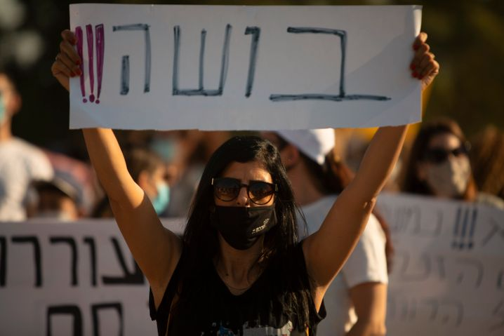 """""""Schande"""" steht auf dem Plakat dieser Demonstrantin"""
