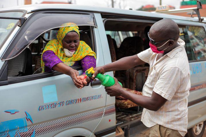 Erste Hilfe gegen Corona: Arbeiter desinfiziert die Hände einer Frau auf einem Sammelpunkt für Taxis