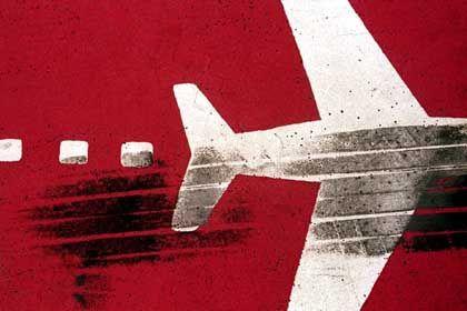 """""""TouchDown"""": Auf dem Vorfeld des Hamburger Flughafens ist auf rotem Grund ein weißes Flugzeug aufgemalt. Darüber zieht sich der schwarze Abdruck eines Jet-Reifens"""