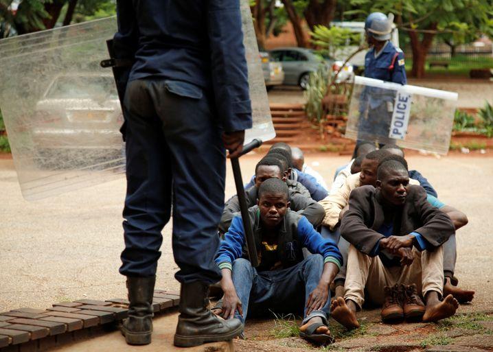 Festgenommene warten auf der Erde sitzend auf ihren Gerichtstermin