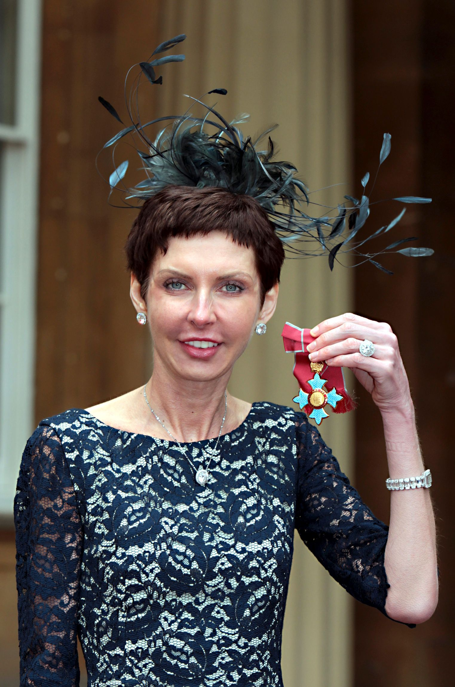 bet365 Chief Executive Denise Coates poses with her CBE medal after being knighted by Britain's Prince Charles at Buckingham Palace in London