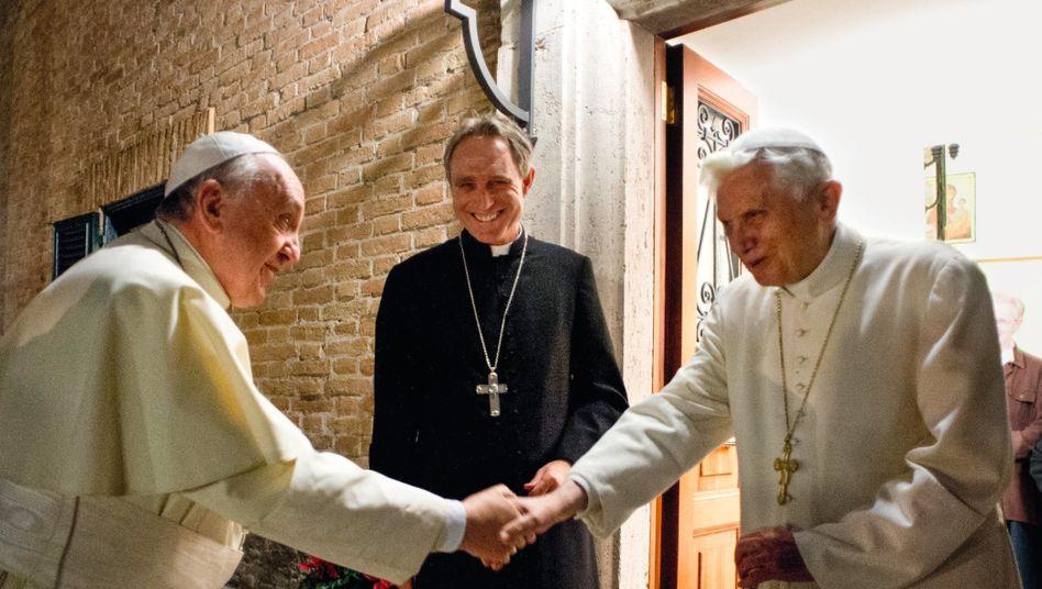 Papst Franziskus, Vorgänger Benedikt XVI. mit Erzbischof Georg Gänswein (M.) im Vatikan 2013:Zerstrittene Heiligkeiten