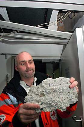 Erdbeben: Matthias Wangler, Helfer des Roten Kreuzes, zeigt im ehemaligen Krankenhaus von Furtwangen einen Betonbrocken, der sich durch das Erdbeben von einer Decke gelöst hatte