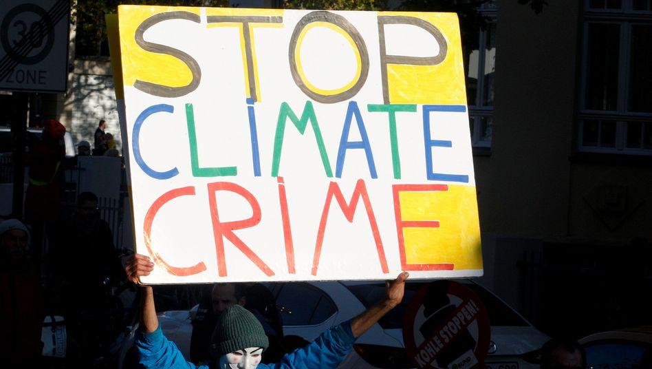 "Demonstrant mit Transparent ""Stop Climate Crime"" in Bonn"