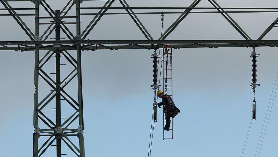 Arbeiter an Überlandleitung: Verbraucher zahlen der Industrie die Zeche