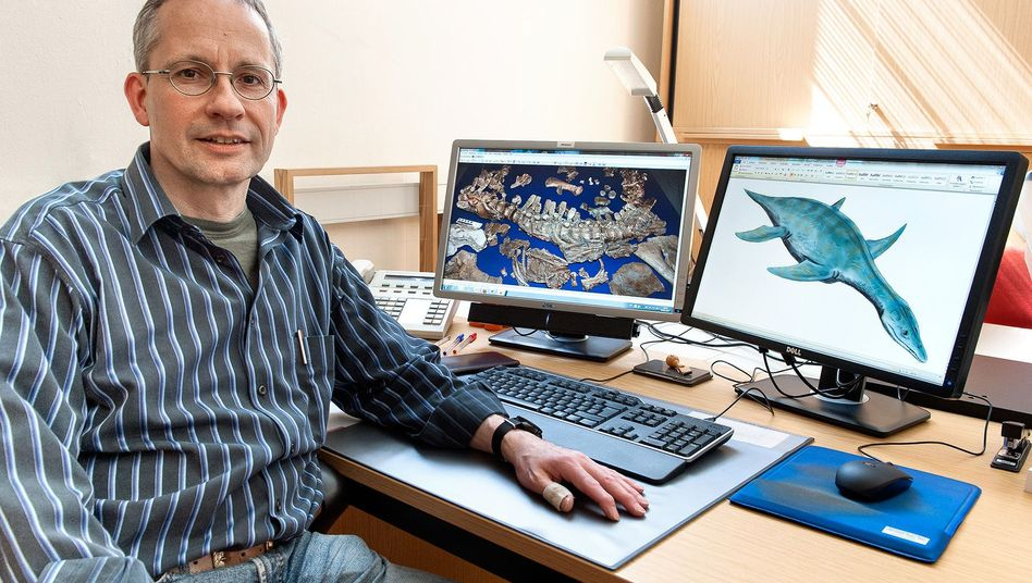 Paleontologist Oliver Hampe sits in front of a photo of the skeleton of the Gronausaurus wegneri and a computer rendering of the species.