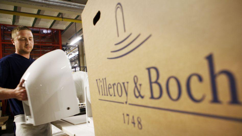 Ein Arbeiter von Villeroy & Boch bereitet Toilettenschüsseln für den Versand vor