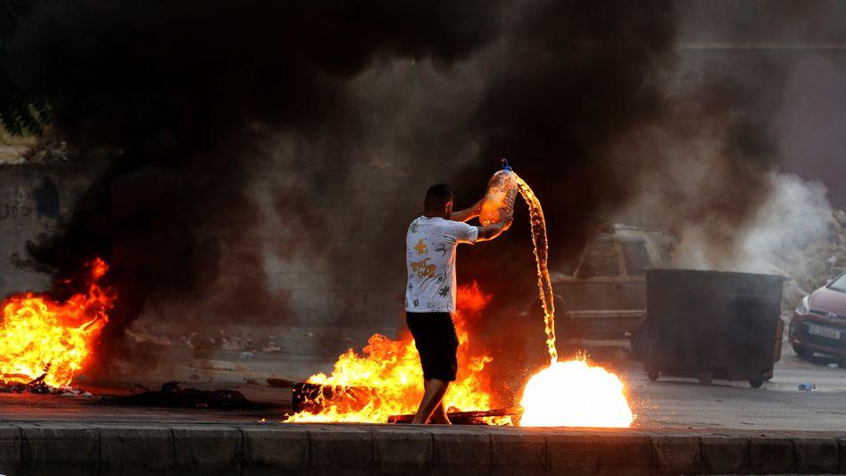 Anti-Regierungs-Protest: Ein Mann gießt Ende Juni Benzin auf eine brennende Barrikade in der libanesischen Hauptstadt Beirut