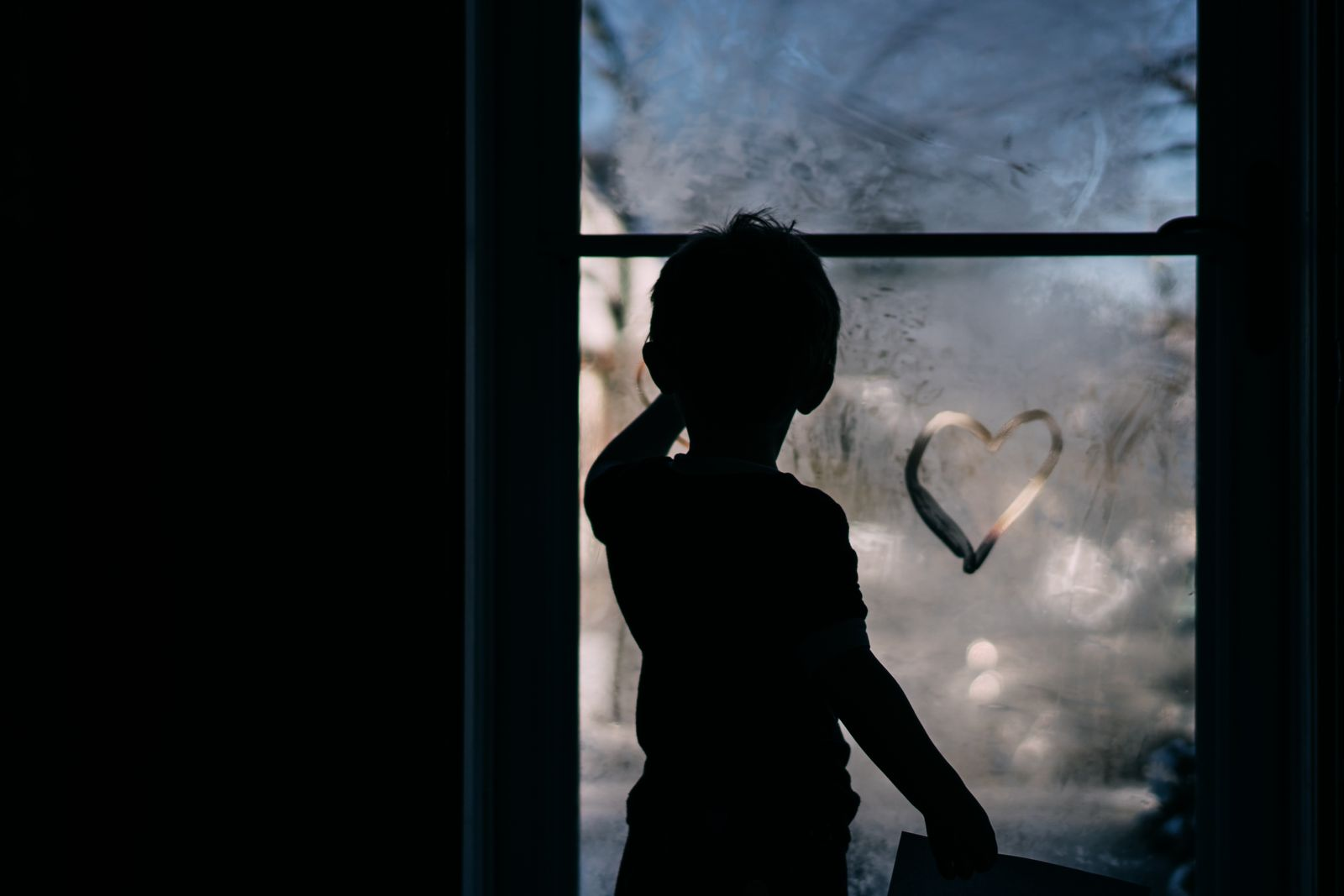 A little boy draws a heart on a foggy storm door.