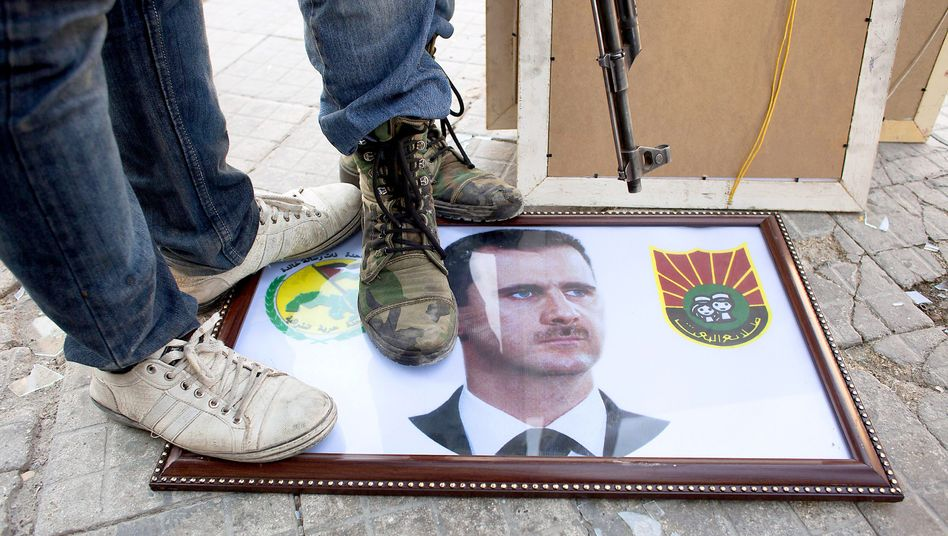 Syrian rebels stand on a picture of President Bashar Assad in the northern city of Aleppo.