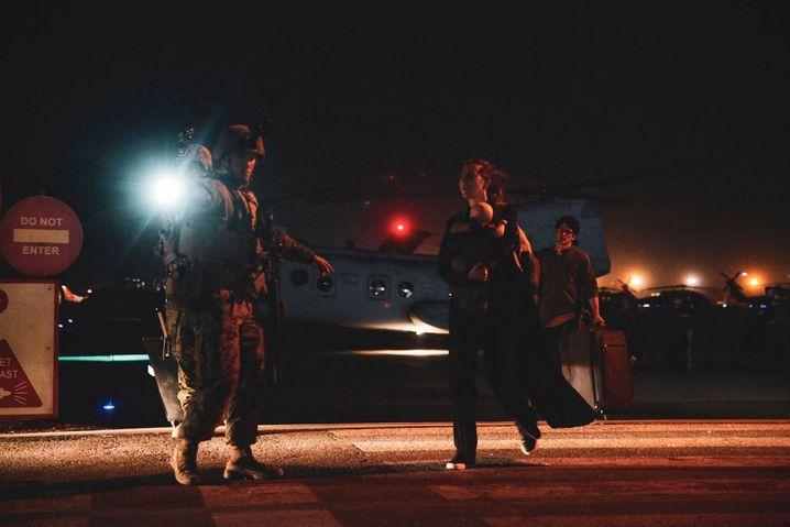Ein US-Soldat weist einer Frau mit Baby den Weg. Die meisten Menschen wurden von staatlichen Rettungsmissionen evakuiert
