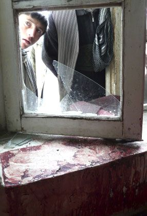 An Afghan boy looks through a broken window at the site of the raid in Imam Sahib.