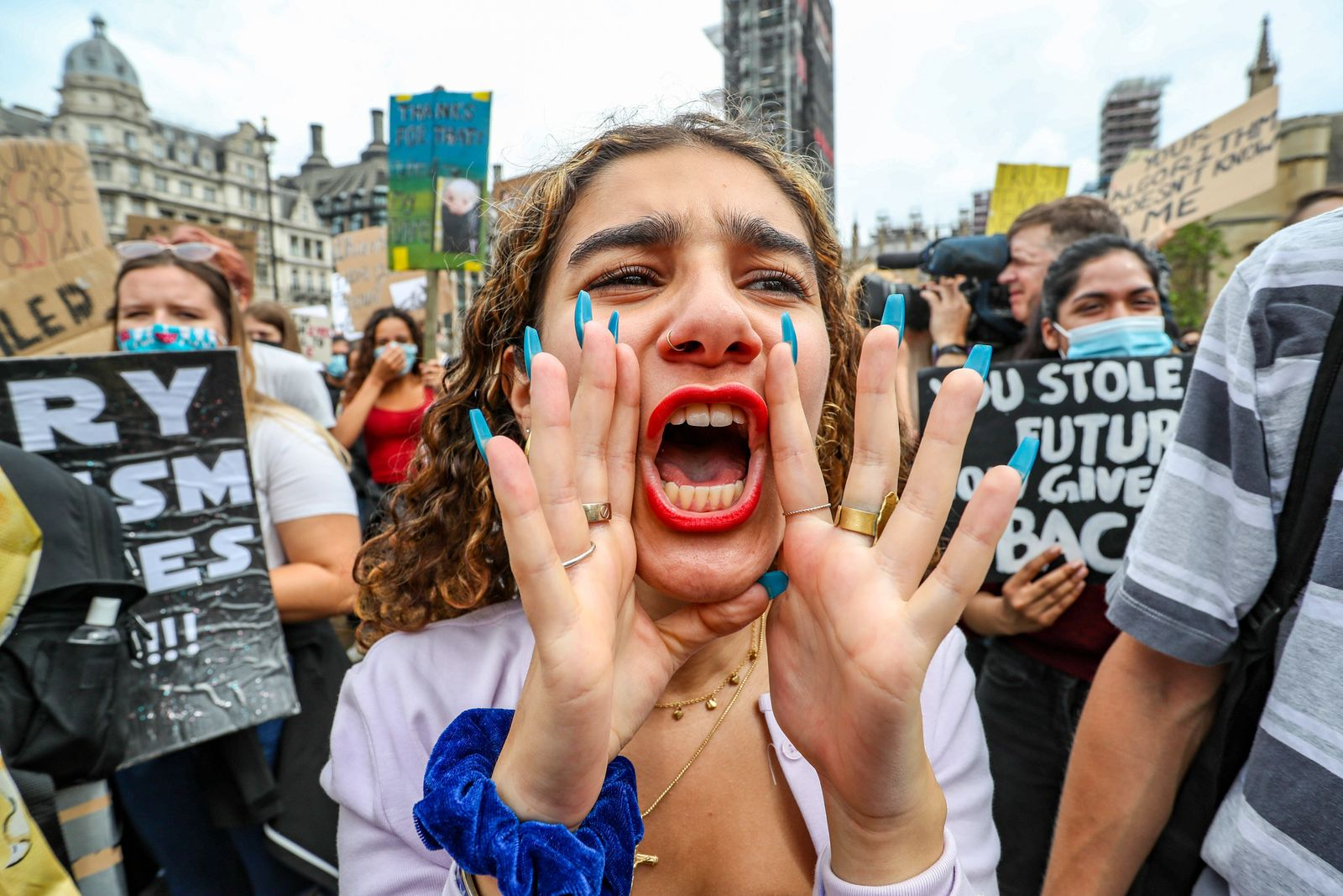 People take part in a peaceful protest in Parliament Square, in Central London on Sunday, Aug 16, 2020 - in response to