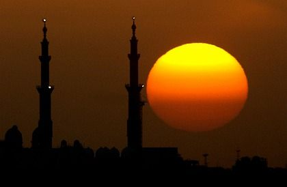 The sun sets behind the Shaikh Zayed Grand Mosque in Abu Dhabi.