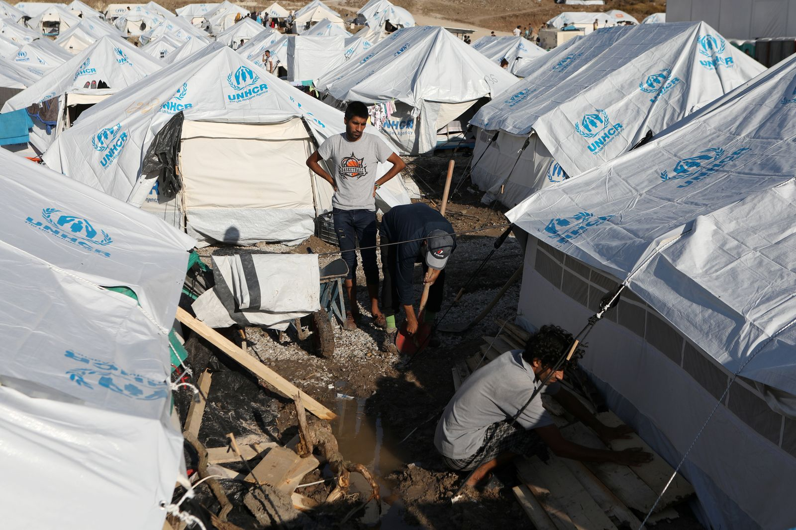 Men repair a tent following a storm, in the Kara Tepe camp for refugees and migrants on the island of Lesbos
