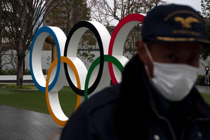 Sicherheitsbeamter vor den Olympischen Ringen in Tokio (Symbolbild)