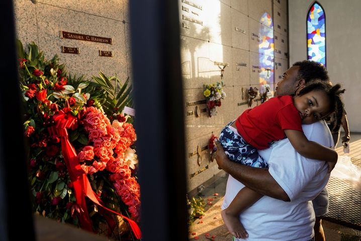 Ein Tod, der viele - und vieles - bewegt: Trauergast mit Kind am Friedhof Houston Memorial Gardens