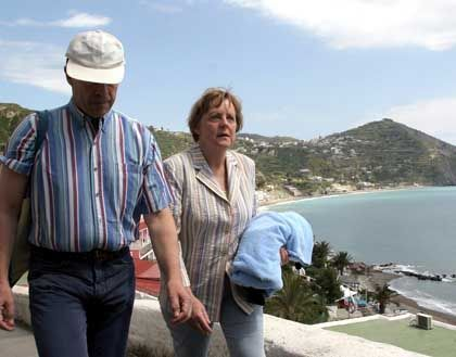 Merkel and her husband Joachim Sauer walking on Ischia during her two-week holiday there.
