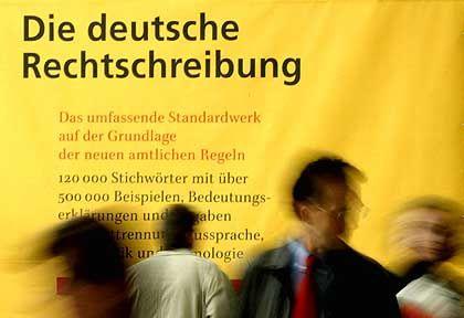 """""""Unausgegorene Reform"""": Besucher der Frankfurter Buchmesse vor einem überdimensionalen Duden"""