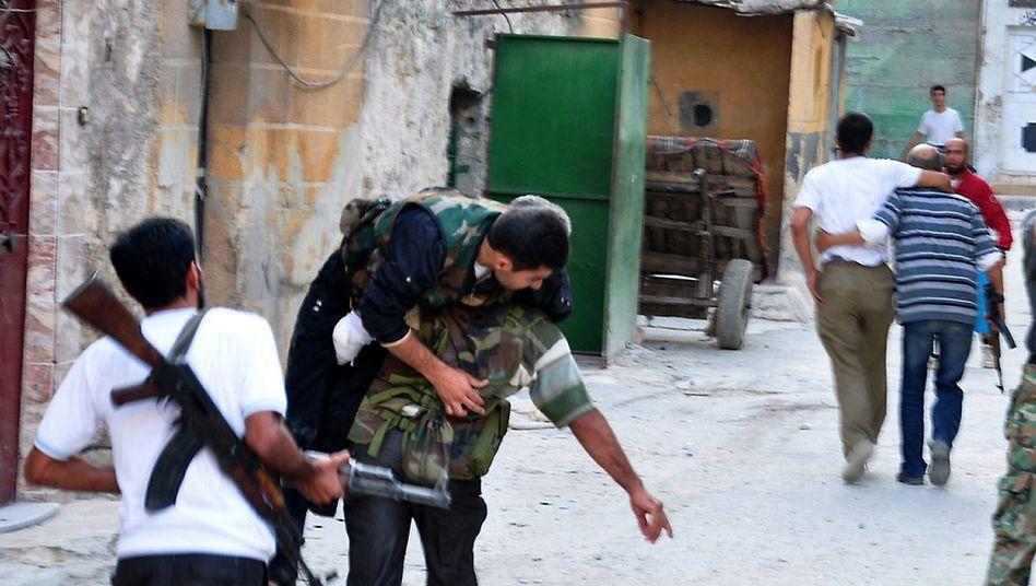 Syrische Rebellen tragen einen Verwundeten in Aleppo: Erbitterte Kämpfe
