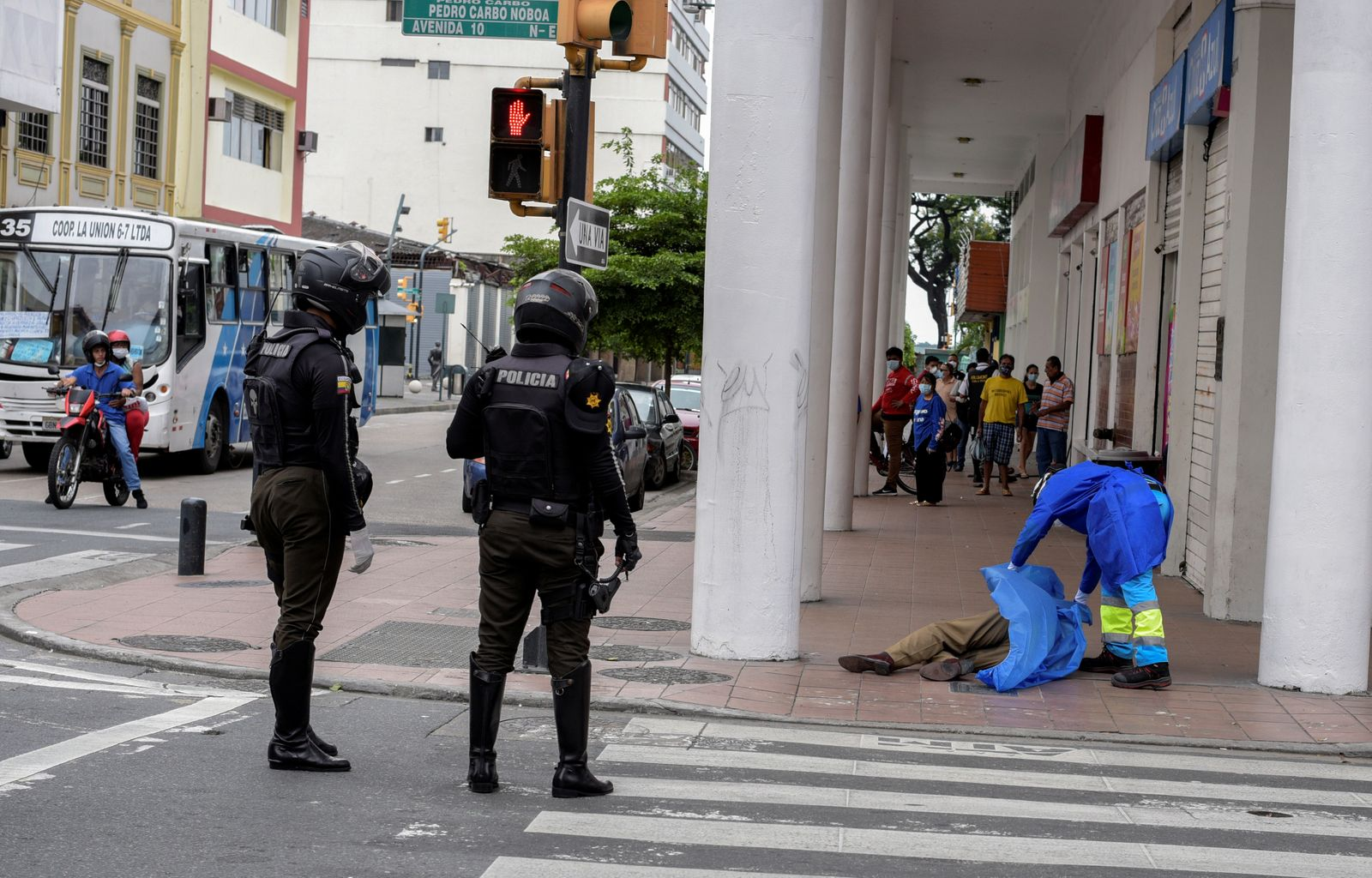 A paramedic covers the dead body of a man who had collapsed on the sidewalk, during the outbreak of the coronavirus disease (COVID-19), in Guayaquil