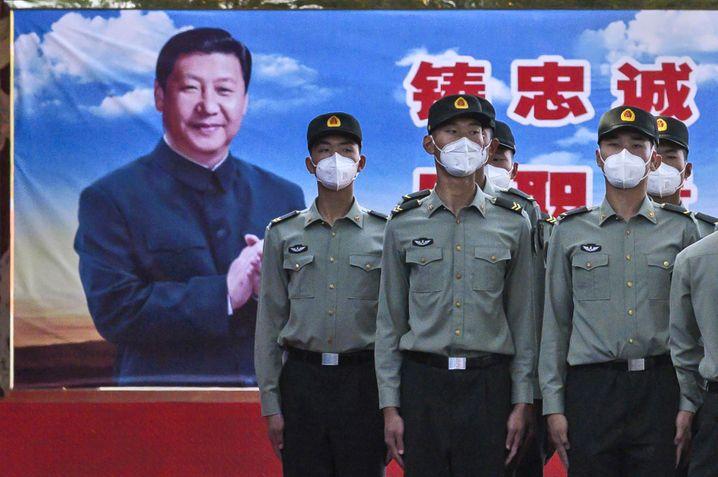 Chinesische Soldaten vor einem Propagandaplakat mit Präsident Xi Jinping