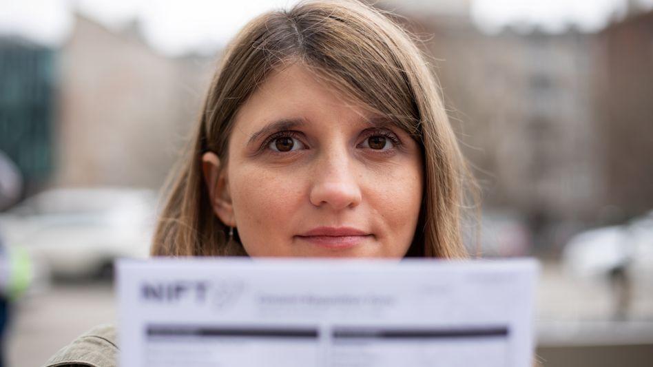 Eine Frau in Warschau mit einer Kopie der Einverständniserklärung des chinesischen Pränataltests Nifty