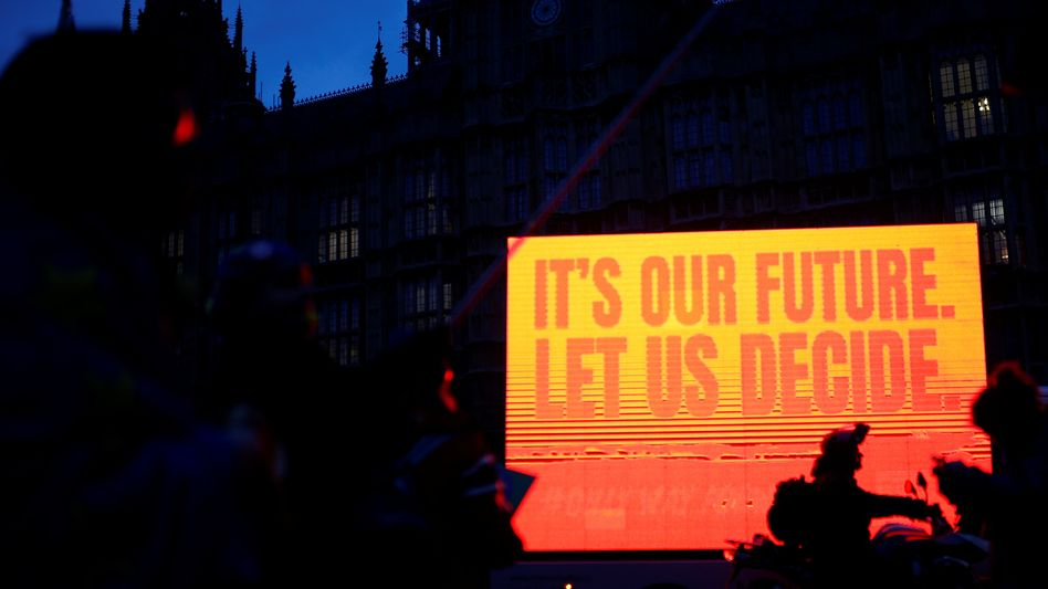 An anti-Brexit sign is seen as protesters demonstrate outside the Houses of Parliament in London