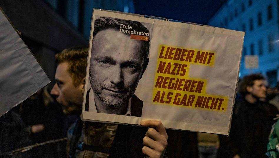 """Ein Demonstrant hält in Berlin ein Schild mit einem Foto von FDP-Chef Christian Lindner und der Aufschrift """"Lieber mit Nazis regieren als gar nicht"""""""