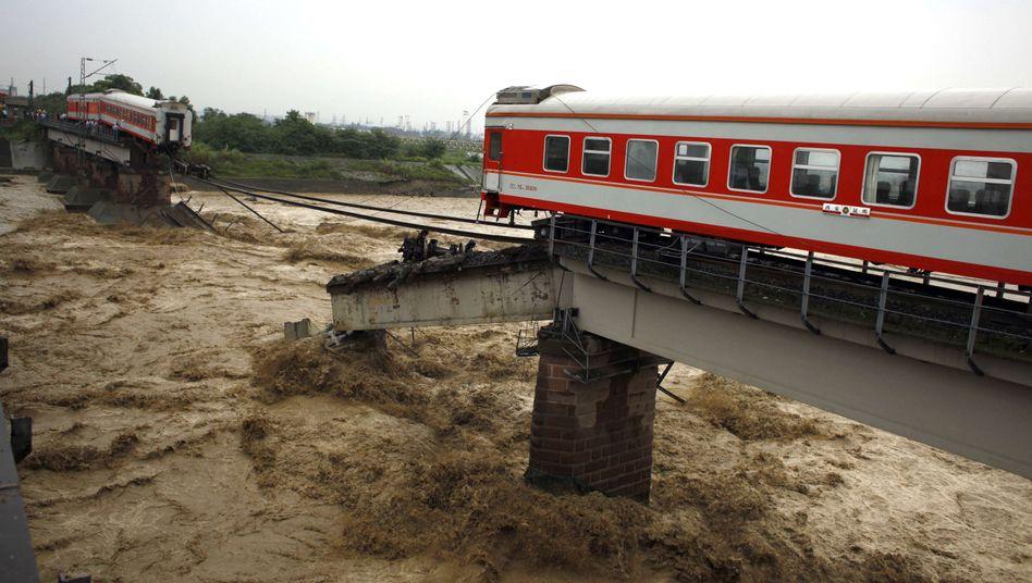 Brückenreste in China: Zwei Waggons stürzten in die Fluten und trieben ab