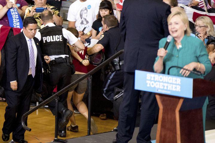 Eine Tierschützerin stürmt die Bühne, der Secret Service schreitet ein.