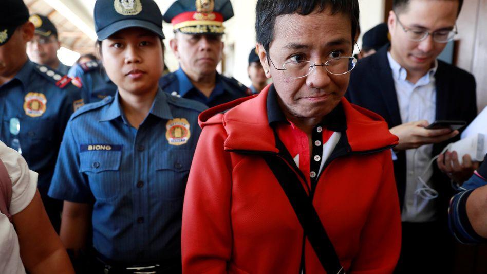 Journalistin Maria Ressa mit Polizei