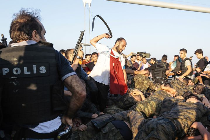 A man uses his belt to hit Turkish soldiers involved in the July 16 coup attempt in Istanbul.