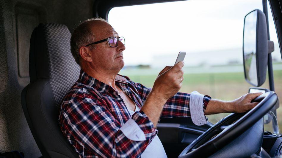 Lkw-Fahrer mit Handy (Symbolbild)