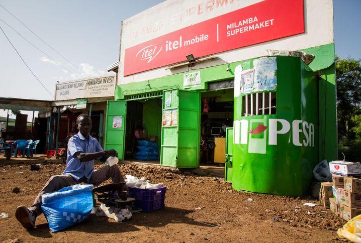 Händler vor einem M-Pesa-Shop.
