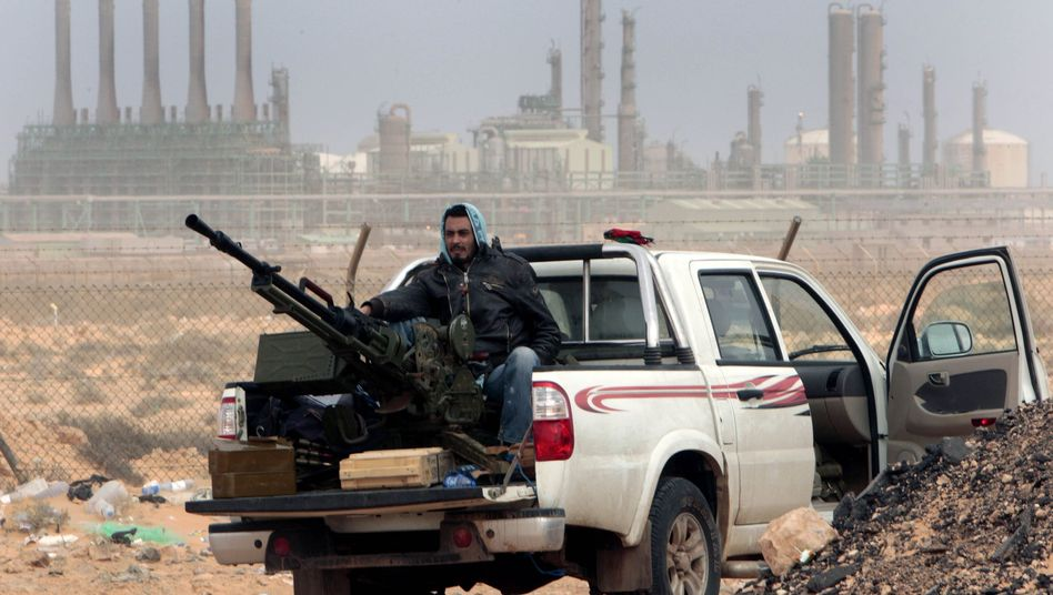 A rebel sits with an anti-aircraft weapon in front of a refinery in the oil town of Ras Lanouf: Europe wants to pressurize Libyan leader Gadhafi, but it continues to buy his oil.