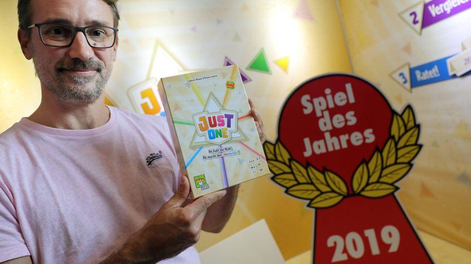 """Spieleautor Bruno Sautter mit seinem Spiel """"Just One"""""""