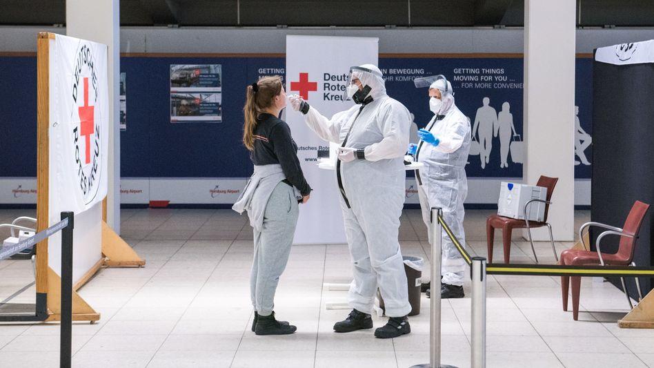 Eine Reisende lässt am Flughafen Hamburg von einem Mitarbeiter des Deutschen Roten Kreuzes (DRK) einen Coronatest machen
