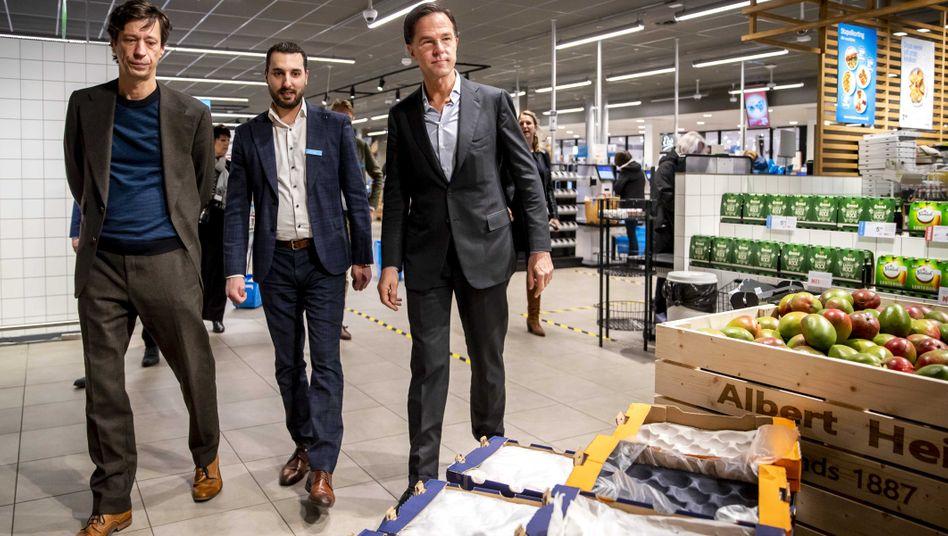 Mark Rutte (rechts) geht durch einen Supermarkt - in der Coronakrise suchte er das Gespräch mit Mitarbeitern