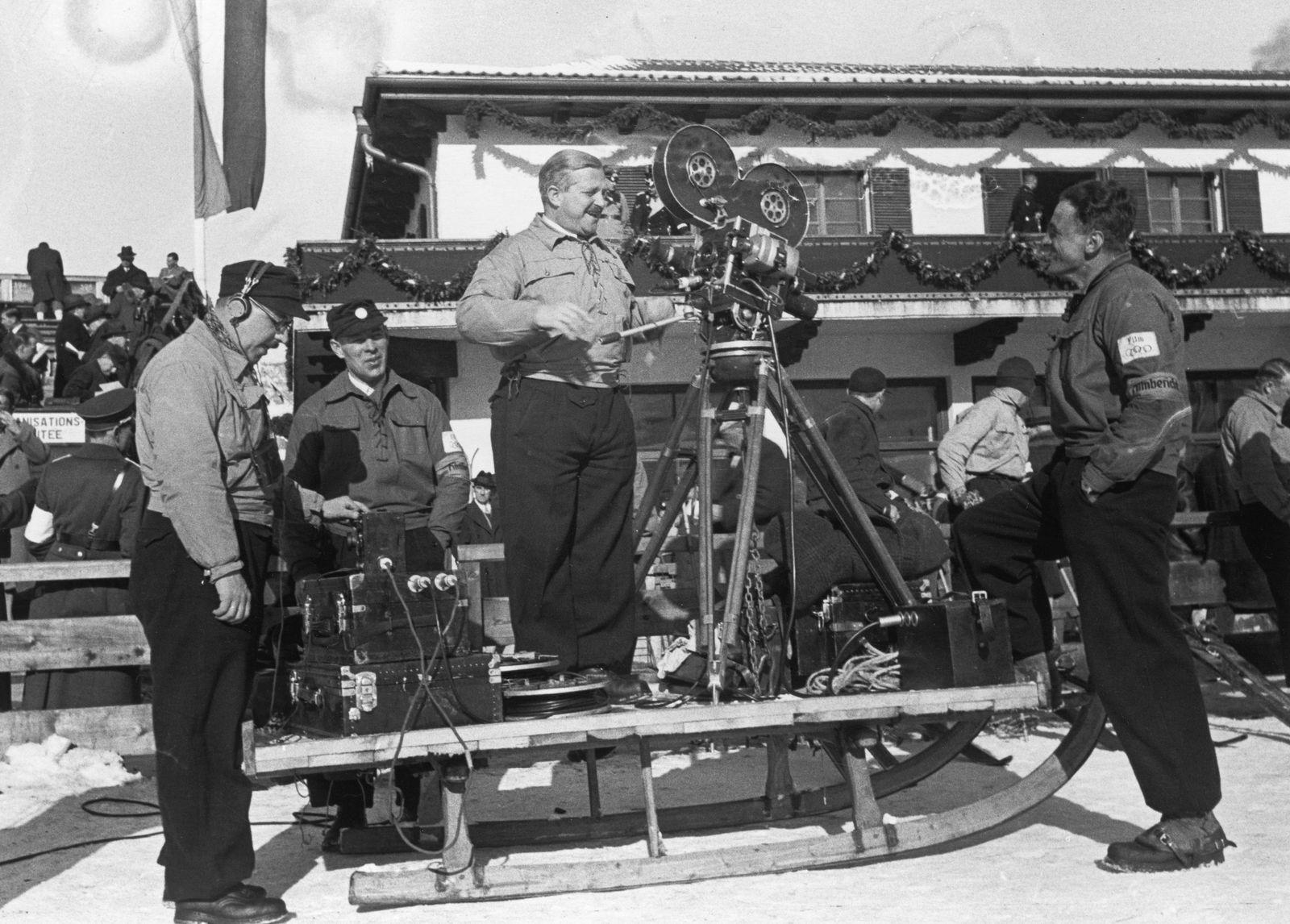 """Das Filmteam von """"Fox Tönender Wochenschau"""" mit Ausrüstung vor dem Olympiahaus"""