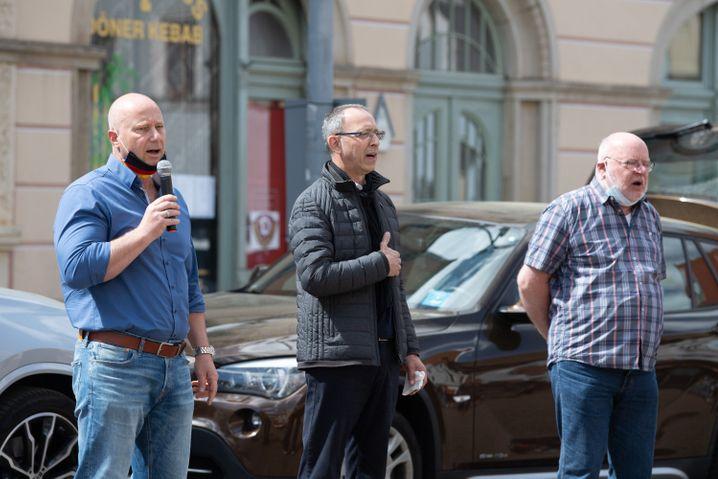 Jan Zwerg (v.l.), Jörg Urban und Lothar Hoffmann von der AfD Sachsen singen zum Abschluss einer Kundgebung in Pirna die Nationalhymne