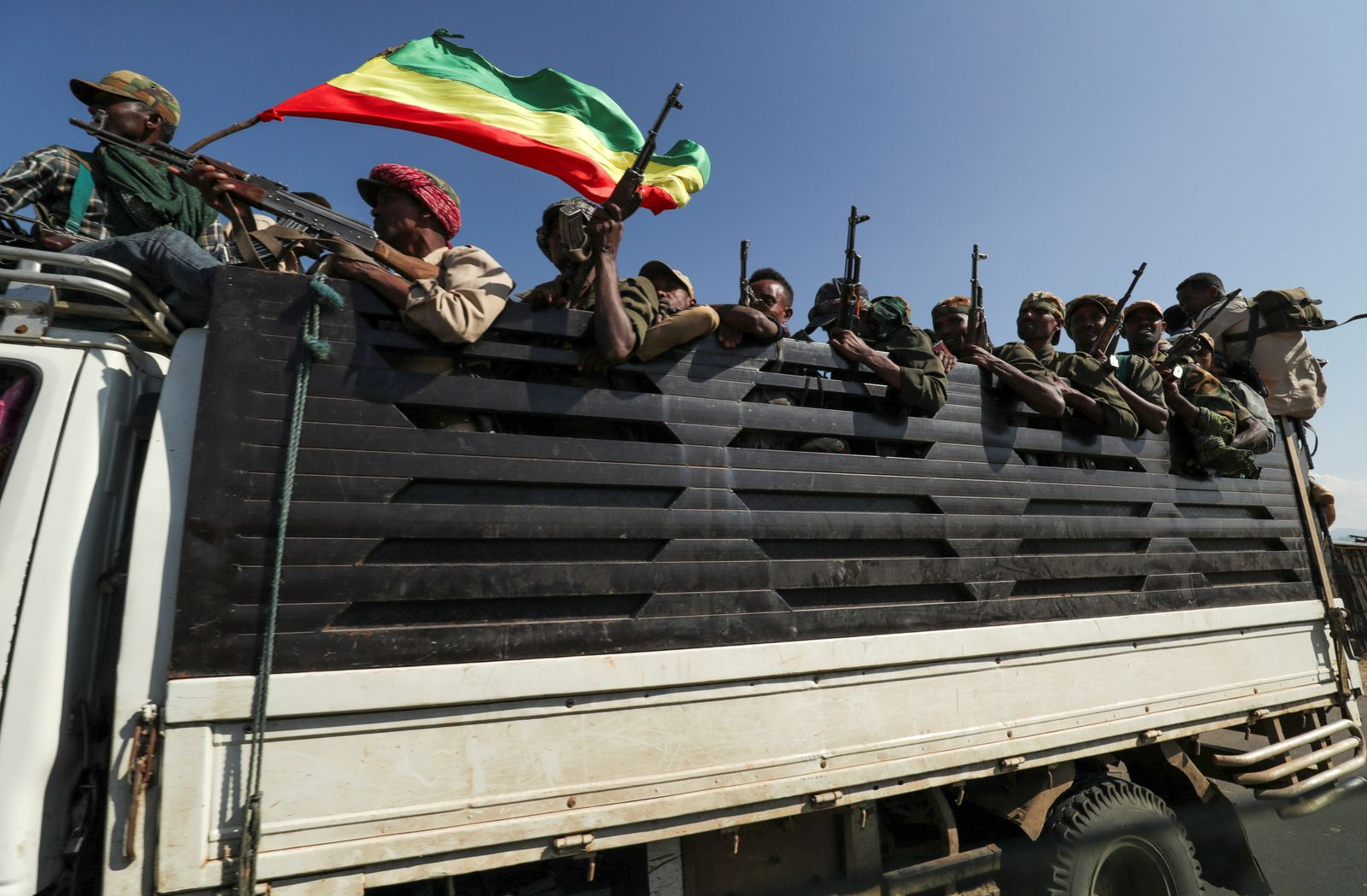 Members of Amhara region militias ride on their truck as they head to face the Tigray People's Liberation Front in Sanja