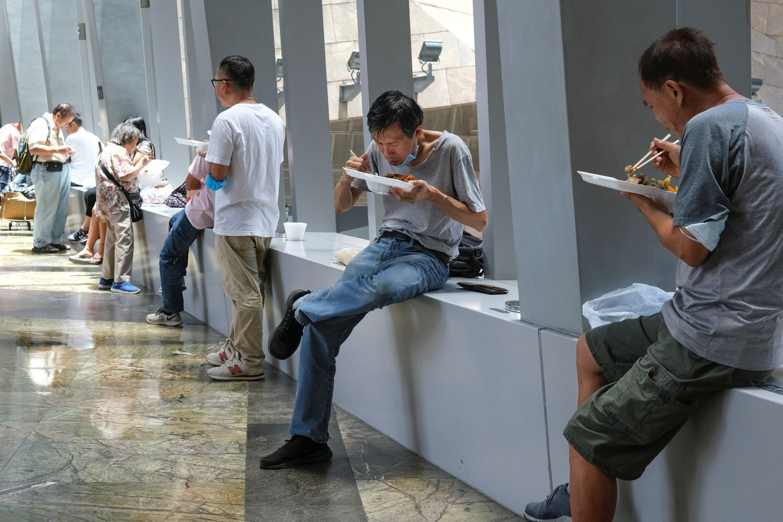 People have lunch at a mall after the government banned dine-in services, following the coronavirus disease (COVID-19) outbreak in Hong Kong