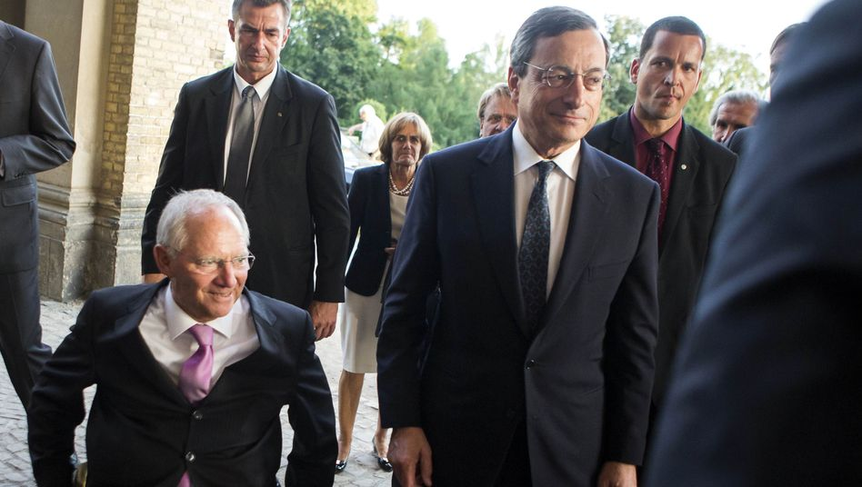 Thursday was a busy day for Mario Draghi (second from right), seen here as he arrives for the M100 Media Prize award ceremony in Potsdam with German Finance Minister Wolfgang Schäuble (left).