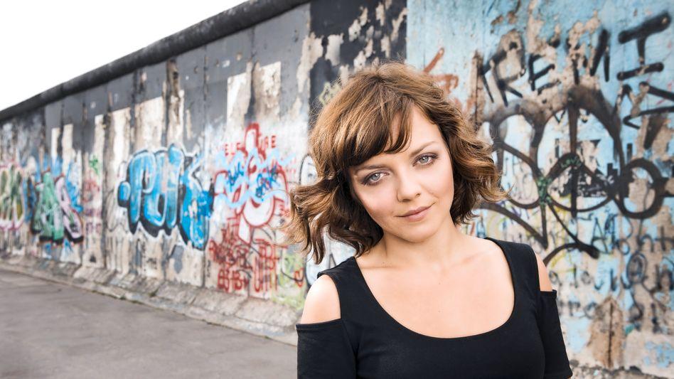 Popstar Annett Louisan vor den Überresten der Berliner Mauer