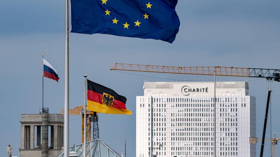 Die Fahnen der EU, der Bundesrepublik und von Russland in Berlin; im Hintergrund die Charité, in der Nawalny behandelt wurde