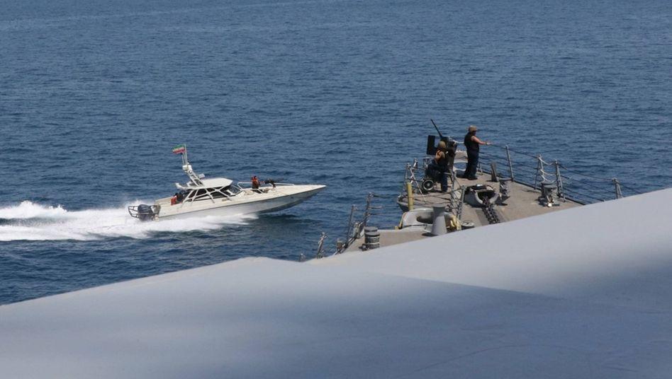 Ein Schnellboot der iranischen Revolutionsgarden passiert ein US-Militärschiff im Persischen Golf